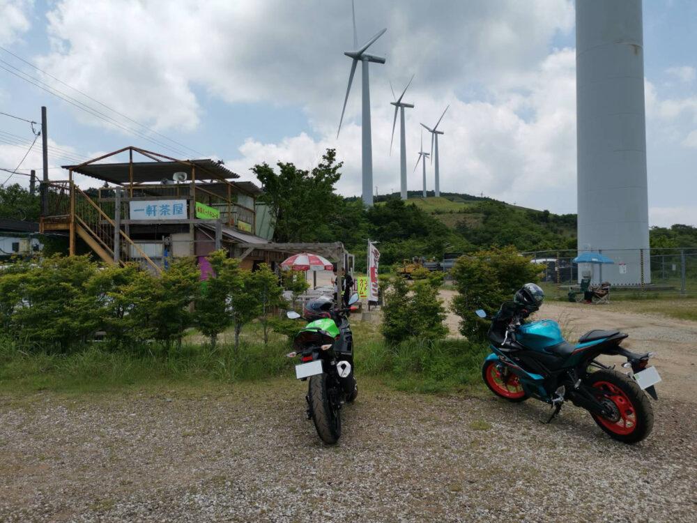 大川原高原。一軒茶屋と風力発電用風車とバイク